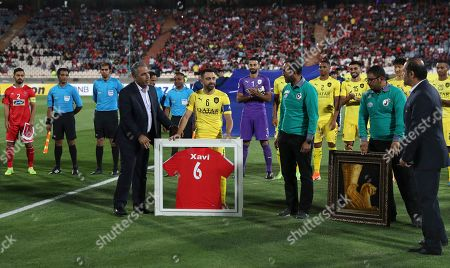 Qatar's Al-Sadd player Xavi Hernández, center, a former Barcelona and Spain's midfielder, is greeted by Iran's Persepolis prior to start their match in AFC Champions League at the Azadi stadium in Tehran, Iran, . Xavi Hernandez retired from soccer as a player. He quit international football in 2014 and left Barcelona one year later after 17 seasons. He has since played for Al-Sadd in Qatar while preparing for a future as a manager