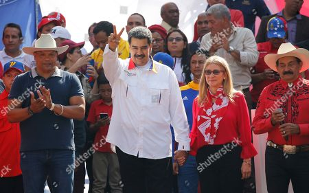 Venezuela's President Nicolas Maduro flashes a victory sign, as he holds hands with his wife Cilia Flores, outside Miraflores presidential palace in Caracas, Venezuela, . Maduro is celebrating the anniversary of his disputed re-election amid a growing humanitarian crisis and political upheaval
