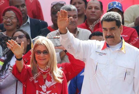 Venezuela's President Nicolas Maduro and his wife Cilia Flores wave to supporters outside Miraflores presidential palace in Caracas, Venezuela, . Maduro is celebrating the anniversary of his disputed re-election amid a growing humanitarian crisis and political upheaval