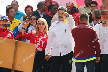 Venezuela's President Nicolas Maduro and his wife Cilia Flores gesture to supporters outside Miraflores presidential palace in Caracas, Venezuela, . Maduro is celebrating the anniversary of his disputed re-election amid a growing humanitarian crisis and political upheaval