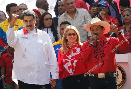 Venezuela's President Nicolas Maduro and his wife Cilia Flores stand with musician Armando Martínez outside Miraflores presidential palace in Caracas, Venezuela, . Maduro is celebrating the anniversary of his disputed re-election amid a growing humanitarian crisis and political upheaval