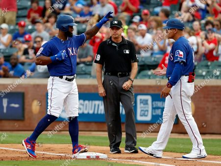 Stock Image of Danny Santana, Hector Ortiz, Andy Fletcher. Texas Rangers' Danny Santana, left, celebrates his run-scoring single as umpire Andy Fletcher, center, and first base coach Hector Ortiz, right, look on in the first inning of a baseball game in Arlington, Texas, . The hit scored Shin-Soo Choo