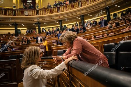 Spains caretaker health minister Maria Luisa Carcedo, right, talks with a Spanish lawmaker at the parliament in Madrid, Spain, . A fragmented Spanish Parliament convened Tuesday after last month's inconclusive general election, including for the first time Catalan politicians released from pre-trial detention for the occasion, as well as two dozen lawmakers from an upstart far-right party