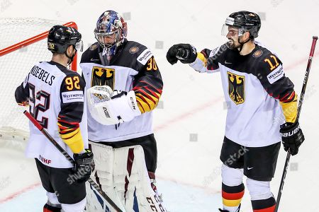 German players (L-R) Marcel Noebels, goalie Philipp Grubauer, and Marco Nowak celebrate after winning the IIHF World Championship group A ice hockey match between Finland and Germany at the Steel Arena in Kosice, Slovakia, 21 May 2019.