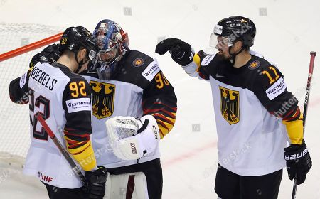 Germany's goaltender Philipp Grubauer, center, celebrates with teammates Marco Nowak, right, and Marcel Noebels, left, during the Ice Hockey World Championships group A match between Germany and Finland at the Steel Arena in Kosice, Slovakia