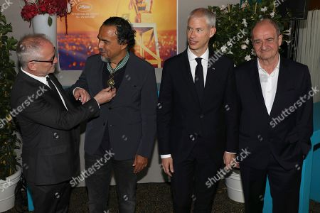 Stock Photo of Festival director Thierry Fremaux, from left, director Alejandro Gonzalez Inarritu, French Culture Minister Franck Riester and festival president Pierre Lescure pose for photographers after awarding Inarritu with the Arts and Letters medal at the 72nd international film festival, Cannes, southern France