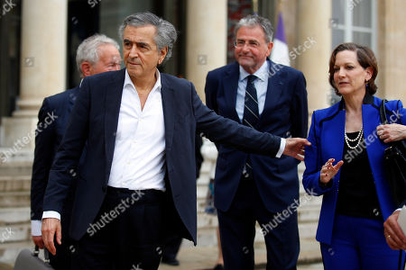 "French philosopher and author Bernard-Henri Levy, second left, walks out with British historian Simon Schama, left, US writer Anne Applebaum, right, and Netherland's philosopher Rob Riemen, second right, after a meeting between French president Emmanuel Macron and other authors and philosophers who signed the tribune ""Europe at risk"" for the upcoming European Union parliament Elections at the Elysee Palace in Paris, France, . The European Union parliament elections will take place in each EU nation between May 23-26 and in France on May 26"