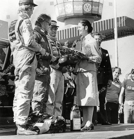 Niki Lauda is greeted by Queen Silvia of Sweden after winning the Formula One Grand Prix. At left Ronnie Peterson and at right Ricardo Patrese.