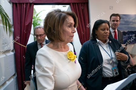 Speaker of the House Nancy Pelosi, D-Calif., departs a meeting with the Democratic Caucus where members heard from former CIA Director John Brennan about the situation in Iran, at the Capitol in Washington, . She is wearing a yellow rose to commemorate the 19th Amendment which guaranteed the vote to women