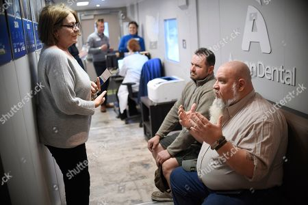 Pam Slack, a representative for U.S. Senator Jeanne Shaheen, D-New Hampshire, discusses veterans issues with patients waiting to receive free dental care on in Keene, N.H. Aspen Dental provides free dental care for local veterans