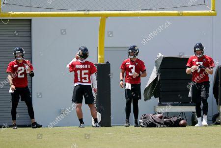 Jacksonville Jaguars quarterbacks, from left, Alex McGough (2), Gardner Minshew II (15), Tanner Lee (3) and Nick Foles (7) take a break during an NFL football practice, in Jacksonville, Fla