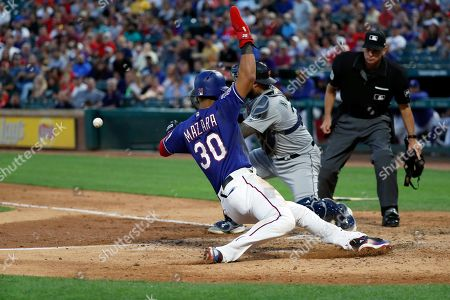 Stock Photo of Nomar Mazara, Omar Narvaez, Andy Fletcher. Seattle Mariners catcher Omar Narvaez (22) attempts the tag as Texas Rangers' Nomar Mazara (30) scores on a sacrifice fly by Asdrubal Cabrera in the fourth inning of a baseball game in Arlington, Texas, . Umpire Andy Fletcher watches the play develop