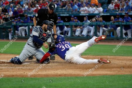 Stock Picture of Nomar Mazara, Omar Narvaez, Andy Fletcher. Seattle Mariners catcher Omar Narvaez (22) attempts the tag as Texas Rangers' Nomar Mazara (30) scores on a sacrifice fly by Asdrubal Cabrera in the fourth inning of a baseball game in Arlington, Texas, . Umpire Andy Fletcher watches the play develop