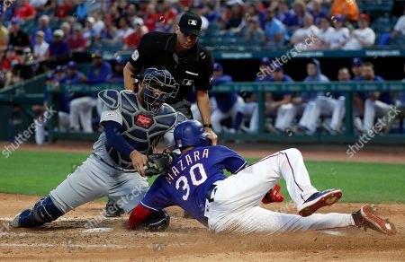 Nomar Mazara, Omar Narvaez, Andy Fletcher. Seattle Mariners catcher Omar Narvaez (22) attempts the tag as Texas Rangers' Nomar Mazara (30) scores on a sacrifice fly by Asdrubal Cabrera during the fourth inning of a baseball game in Arlington, Texas, . Umpire Andy Fletcher watches