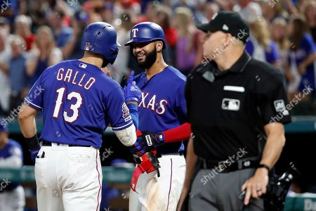 Stock Image of Joey Gallo Nomar Mazara, Andy Fletcher. Texas Rangers' Joey Gallo (13) and Nomar Mazara, center, celebrate a two-run home run by Gallo against the Seattle Mariners that scored Mazara, as umpire Andy Fletcher stands by the plate during the eighth inning of a baseball game in Arlington, Texas