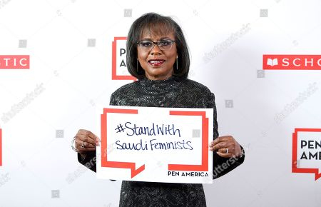PEN courage award recipient Anita Hill poses holding a sign in support of jailed Saudi women's rights activists Nouf Abdulaziz, Loujain Al-Hathloul and Eman Al-Nafjan at the 2019 PEN America Literary Gala at the American Museum of Natural History, in New York