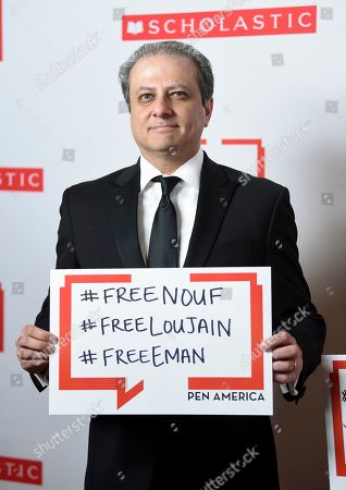 Former United States Attorney for the Southern District of New York and author Preet Bharara poses holding a sign in support of jailed Saudi women's rights activists Nouf Abdulaziz, Loujain Al-Hathloul and Eman Al-Nafjan at the 2019 PEN America Literary Gala at the American Museum of Natural History, in New York