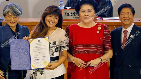 """Imee Marcos, Irene Marcos-Araneta, Imelda Marcos, Ferdinand """"Bongbong"""" Marcos Jr. Newly-elected Senator Imee Marcos, second from left, holds her election certificate as she poses with her family at a ceremony in suburban Pasay city, south of Manila, Philippines . The Philippine president's allies won a majority of the 12 Senate seats at stake in the May 13 midterm elections while the opposition's shutout heralds a stronger grip on power by a leader accused of massive human rights violations. From left, sister Irene Marcos-Araneta, mother former first lady Imelda Marcos, and brother former senator Ferdinand """"Bongbong"""" Marcos Jr. The Marcoses ruled the country for 20 years until they were ousted via a """"People Power Revolution"""" in 1986"""
