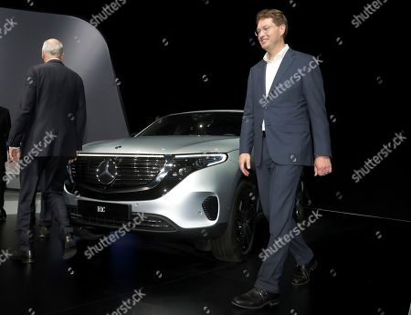 Daimler CEO Dieter Zetsche, left, and incoming Daimler CEO Ola Kaellenius, right, walk past a Mercedes car prior to the annual shareholder meeting of the car manufacturer Daimler in Berlin, Germany