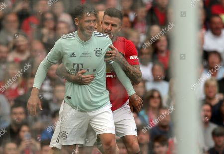 David Beckham of Manchester United holds onto Martin Demichelis of Bayern Munich