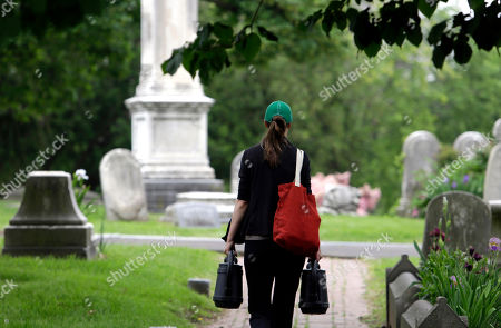 Stock Image of Volunteer Jennifer Walker carries water to the Keen family plot she tends at the Woodlands Cemetery in Philadelphia. The cemeteries of yore existed as much the living as for the dead. And a handful of these 19th century graveyards are restoring the bygone tradition of cemetery gardening