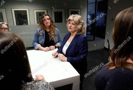 Stock Picture of Business owner Meloney Perry, center right, of Perry Law, speaks with members of her staff, attorney Karla Roush, left front, office manager Lisa Amerson, left rear, paralegal Michelle Smith, center left, and paralegal Brooke Bailey, right, as they congregate in the kitchen area at her law firm in Dallas