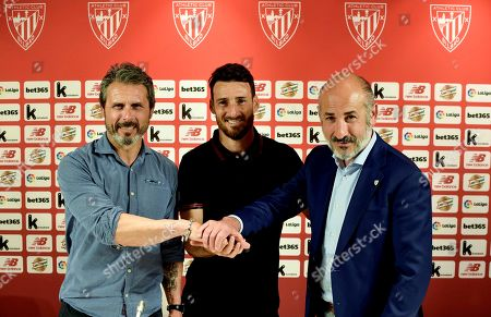 Athletic Bilbao's Spanish striker Aritz Aduriz (C) poses next to Athletic Bilbao's President Aitor Elizegi (R) and the club's Sports Director Rafa Alkorta (L) during his contract renewal signing ceremony in Bilbao, Basque Country, northern Spain, 22 May 2019. Aduriz renewed his contract for one more season.
