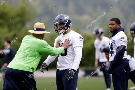 Seattle Seahawks defensive coordinator Ken Norton Jr., left, works with Austin Calitro, center, as Bobby Wagner looks on during an NFL football practice, in Renton, Wash
