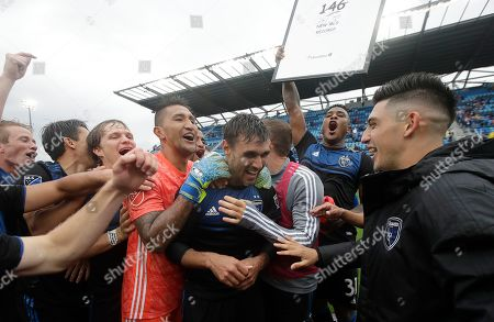 San Jose Earthquakes forward Chris Wondolowski, center, celebrates with teammates after the Earthquakes defeated the Chicago Fire in an MLS soccer match in San Jose, Calif., . Wondolowski scored four times to pass Landon Donovan for most career MLS goals