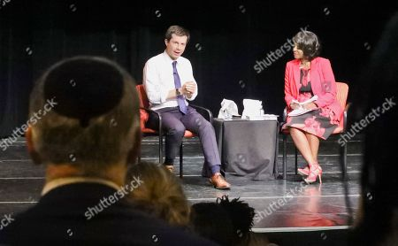 """Democratic presidential candidate Mayor Pete Buttigieg, left, South Bend, Indiana, speaks with NY1 news anchor Cheryl Wills, during the Queens Democratic party's first in a series of """"presidential fireside chat""""-- a town hall forum meant to bring candidates before the country's most diverse county, at LaGuardia Community College in New York"""