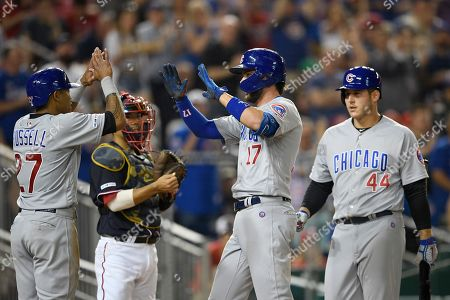 Chicago Cubs' Kris Bryant (17) celebrates his two-run home run with Addison Russell (27) and Anthony Rizzo (44) during the seventh inning of a baseball game as Washington Nationals catcher Kurt Suzuki, second from left, looks, in Washington