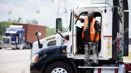 Leon Brown stands by his tractor-trailer after making a delivery from a distribution center to the Port of Savannah, in Garden City, Ga