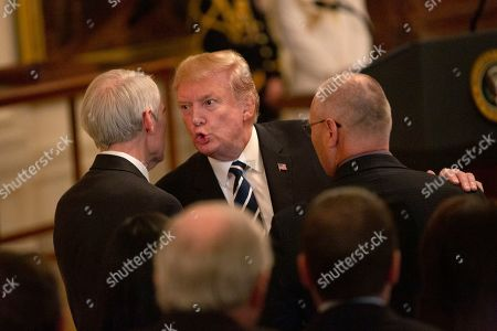 President Donald Trump speaks to United States Senator Robert Portman (Republican of Ohio) after awarding the Medal of Valor to 13 firefighters and police officers from the Azusa Police Department at a ceremony at the White House.