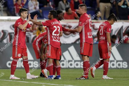 New York Red Bulls forward Brian White, left, celebrates with Cristian Casseres Jr. (23) and others after his shot was deflected by Vancouver Whitecaps midfielder Andy Rose, not visible, into his own net for a goal during the second half of an MLS soccer match, in Harrison, N.J. The teams tied 2-2