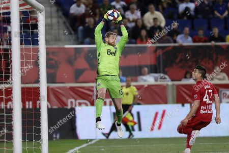Vancouver Whitecaps goalkeeper Zac MacMath, left, jumps up to catch the ball while New York Red Bulls forward Brian White watches during the first half of an MLS soccer match, in Harrison, N.J
