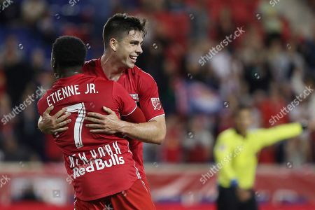 New York Red Bulls forward Brian White, center, hugs New York Red Bulls midfielder Derrick Etienne Jr. after scoring a goal during the first half of an MLS soccer match against the Vancouver Whitecaps, in Harrison, N.J