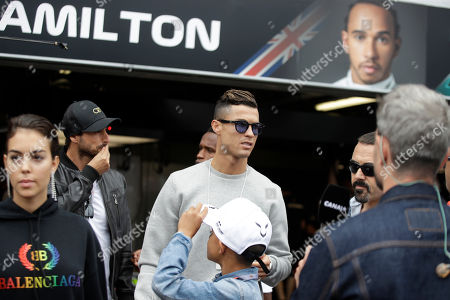 Cristiano Ronaldo, center, with his partner Georgina Rodriguez, left, and his son Cristiano Ronaldo Jr walk at the pit line ahead of the second practice session at the Monaco racetrack, in Monaco, . The Formula one race will be held on Sunday
