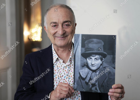 Sir Tony Robinson holds a picture of himself at a young boy