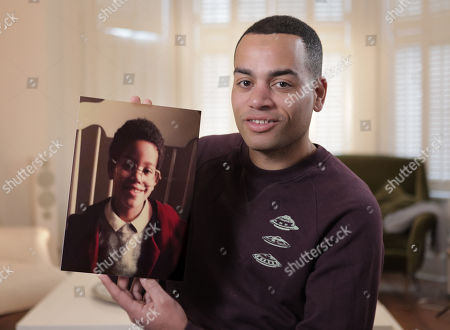 Ben Bailey Smith holds a picture of himself as a young boy