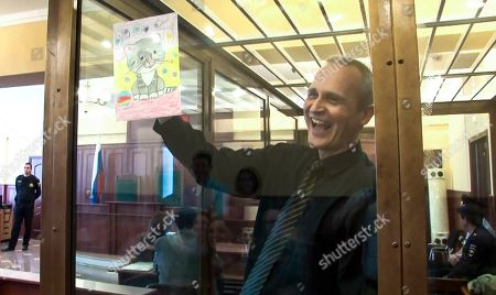 In this image taken from video, Dennis Christensen shows a picture in a court room in Oryol, Russia, . A court in Russia has ruled that Danish Jehovah's Witness, Dennis Christensen, must stay in prison for the next six years. The court in western Russia on Thursday May 23, 2019, turned down Dennis Christensen's appeal against February's verdict that found him guilty of participating in the activities of an extremist organization