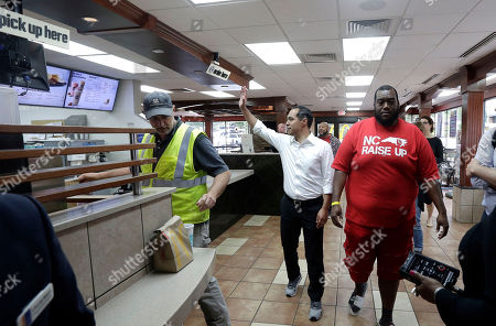 Presidential candidate and former U.S. Department of Housing and Urban Development Julian Castro waves to employees inside of a McDonald's during a rally with employees and other activists demanding fairer pay, better working conditions, and the right to unionize in Durham, N.C