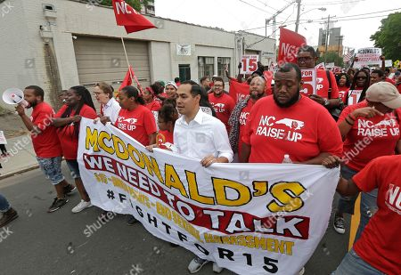 Stock Photo of Presidential candidate and former U.S. Department of Housing and Urban Development Julian Castro, center, rallies with McDonald's employees and other activists demanding fairer pay, better working conditions, and the right to unionize in Durham, N.C