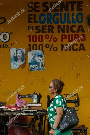 "A woman walks past a tailor's shop featuring photos of Nicaraguan President Daniel Ortega and first lady Rosario Murillo, at the Roberto Huembes market where some vendors partook in a general strike aimed at pressuring the government to free political prisoners in Managua, Nicaragua, . The words on the wall read in Spanish ""Feeling the pride in being 100% pure Nicaraguan"