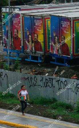 "A woman walks past abandoned trailers that read in Spanish ""Mobile clinics,"" covered with photos of Nicaraguan President Daniel Ortega and first lady Rosario Murillo, on the day of a general strike aimed at pressuring the government to free political prisoners in Managua, Nicaragua"