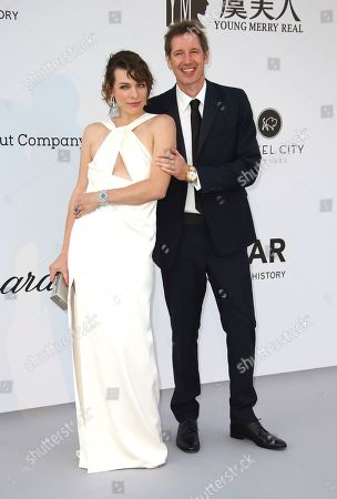 Mila Jovovich, Paul Anderson. Mila Jovovich and her husband Paul Anderson pose for photographers upon arrival at the amfAR, Cinema Against AIDS, benefit at the Hotel du Cap-Eden-Roc, during the 72nd international Cannes film festival, in Cap d'Antibes, southern France