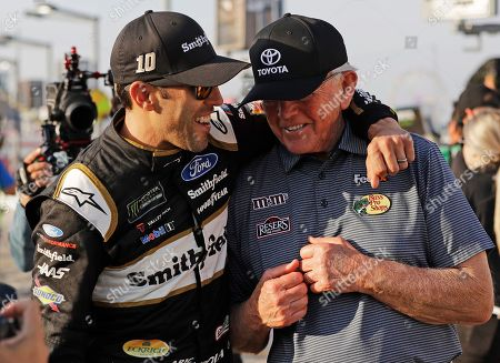 Joe Gibbs, Aric Almirola. Team owner Joe Gibbs, right, is congratulated by Aric Almirola for being named to the NASCAR Hall of Fame, as they walk down pit road before qualifications for Sunday's NASCAR Cup Series auto race at Charlotte Motor Speedway in Concord, N.C