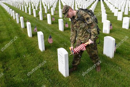 """Stock Picture of Cpl. Matthew Munie, of Jackson, Mich., and a member of the 3d U.S. Infantry Regiment also known as The Old Guard, places a flags in front of a headstone for """"Flags-In"""" at Arlington National Cemetery in Arlington, Va., to honor the Nation's fallen military heroes"""