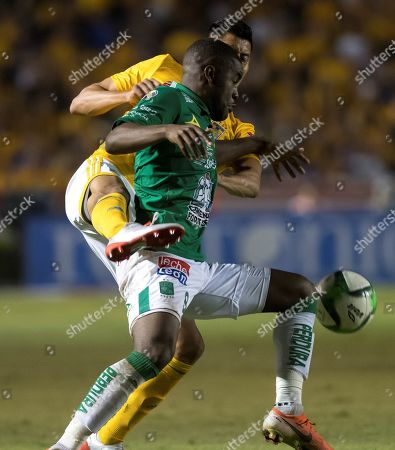 Tigres UANL's Hugo Ayala (back) vies for the ball with Joel Campbell (front) of Leon during the first leg of the Clausura 2019 final between the Tigres and Leon held at the University Stadium in Monterrey, Mexico, 23 May 2019.