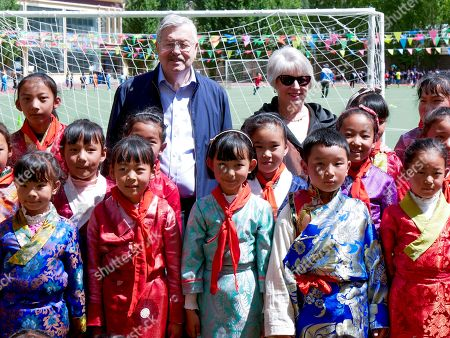 And released by the U.S. Embassy in Beijing, U.S. Ambassador to China Terry Branstad and his wife Christine pose for a group photo with schoolchildren as he visits an elementary school in Lhasa in western China's Tibet Autonomous Region. The U.S. ambassador to China made a rare visit to Tibet this week to meet local officials and raise concerns about restrictions on Buddhist practices and the preservation of the Himalayan region's unique culture and language