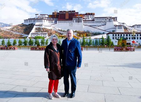 Stock Image of And released by the U.S. Embassy in Beijing, U.S. Ambassador to China Terry Branstad and his wife Christine pose for a photo in front of the Potala Palace in Lhasa in western China's Tibet Autonomous Region. The U.S. ambassador to China urged Beijing to engage in substantive dialogue with exiled Tibetan Buddhist leader the Dalai Lama during a visit to the Himalayan region over the past week, the Embassy said Saturday